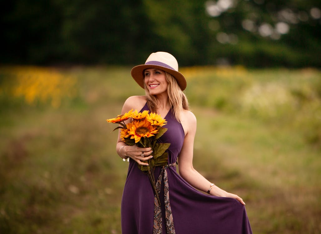 Photo of Smiling Woman in Purple Dress Holding Sunflower Bouquet